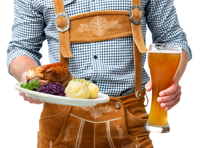Food and drinks are served by waiter wearing traditional Bavarian leather trousers 스톡 콘텐츠