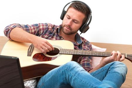 ソファの自宅のラップトップとギターを弾く男
