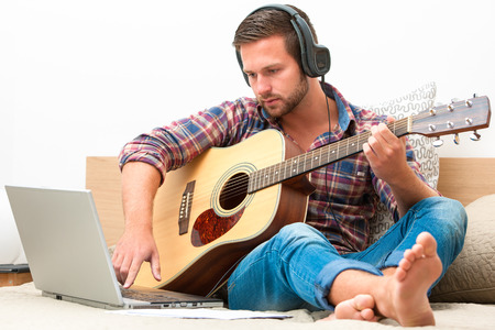 young musician: Man on sofa playing the guitar with laptop at home