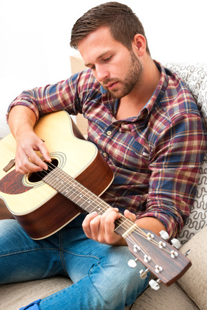 fingering: Man on sofa playing the guitar with laptop at home