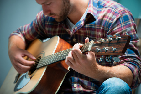 close-up van een mannelijke muzikant spelen akoestische gitaar