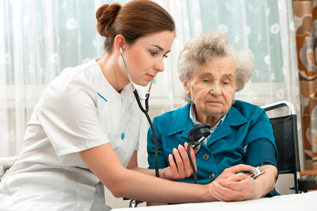 Female nurse measuring blood pressure of senior woman photo