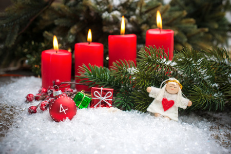 christmas greeting: Christmas tree branches and candle for advent season four candles burning