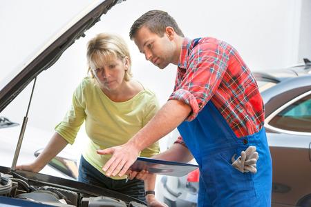 자동 수리점 자동차 정비공과 여성 고객 스톡 콘텐츠