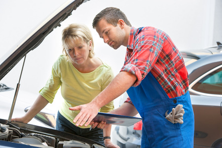 car hood: Auto mechanic and female customer in auto repair shop