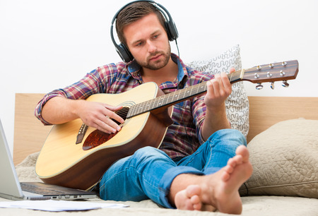Man on sofa playing the guitar with laptop at home photo