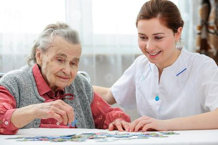 working at home: Enfermera cuidado de los ancianos jugando rompecabezas con la mujer mayor en hogar de ancianos