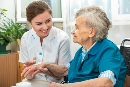 aide � la personne: Infirmi�re aide une femme �g�e avec soins de la peau et des mesures d'hygi�ne � la maison Banque d'images