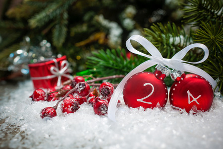 Christmas background with ornaments, gift box, berries and fir in snow photo