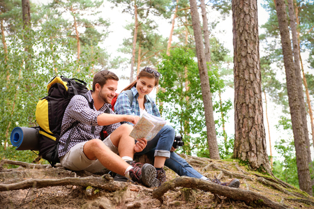 camping equipment: Happy couple going on a hike together in a forest Stock Photo