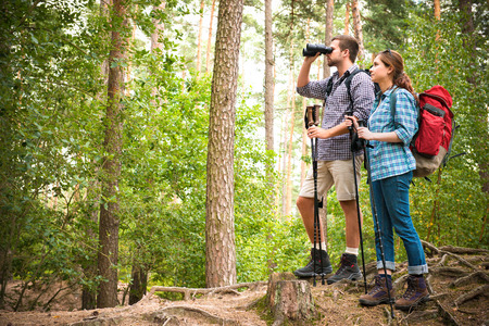 adventuring: Happy couple going on a hike together in a forest Stock Photo