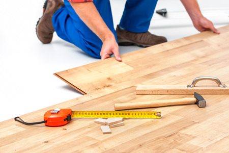 fitting: carpenter worker installing laminate flooring in the room Stock Photo