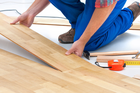 carpenter worker installing laminate flooring in the room Banco de Imagens
