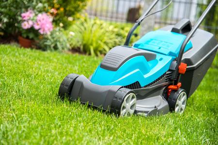 jardinero: Cortadora de césped en un prado verde. Equipos de jardinería