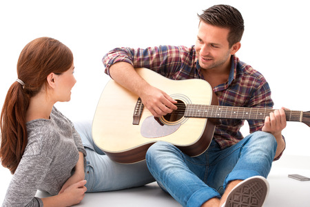 amigos abrazandose: Hermosa joven pareja descansando en casa y tocar la guitarra