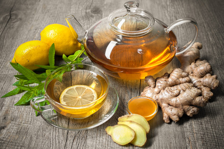 Cup of ginger tea with honey and lemon on wooden table Imagens