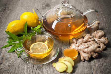 jengibre: Taza de té de jengibre con miel y limón en la mesa de madera