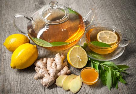 木製のテーブルにレモンと蜂蜜生姜茶のカップ