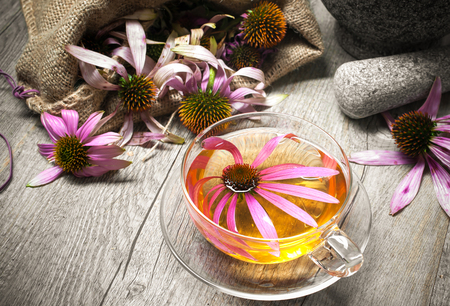 alternative: Echinacea purpurea. Cup of echinacea  tea on wooden table