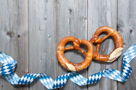 Bavarian pretzels with ribbon on wooden board as a background for Oktoberfest photo