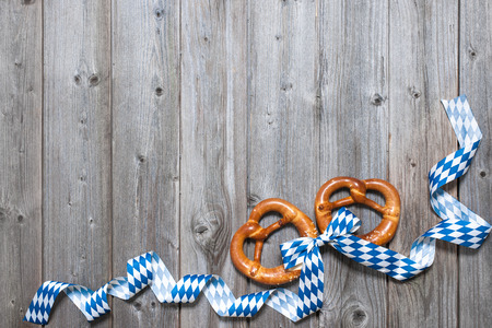 Bavarian pretzels with ribbon on wooden board as a background for Oktoberfest Stock Photo