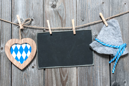 Message, bavarian hat and heart hanging on the clothesline against wooden board. Background for Oktoberfest