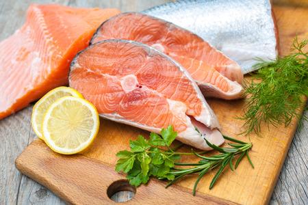 Filetes de pescado de salmón sin procesar con las hierbas frescas en la tabla de cortar Foto de archivo - 32102143