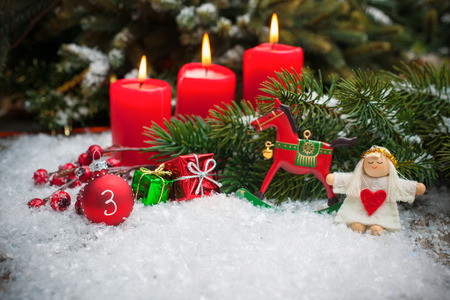 Christmas tree branches and candle for advent season three advent candles burning photo