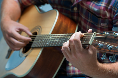 close up of a male musician playing acoustic guitar photo