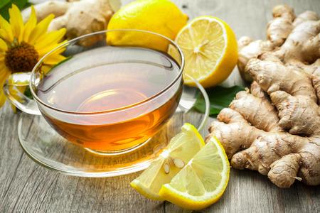 木製のテーブルにレモンと生姜茶のカップ