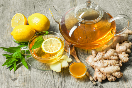 healing plant: Cup of ginger tea with honey and lemon on wooden table Stock Photo
