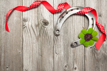 luckiness: Holidays background with horseshoe, shamrock and red ribbon on old wooden