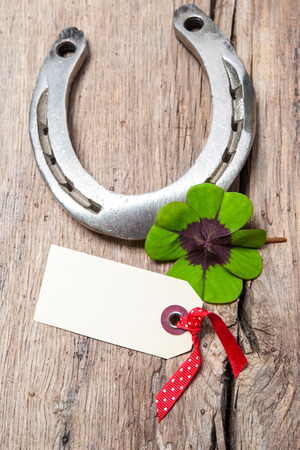 four leaved: Horseshoe and four leaf clover with empty tag on old wooden