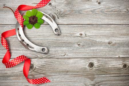 mojo: Holidays background with horseshoe, shamrock and red ribbon on old wooden