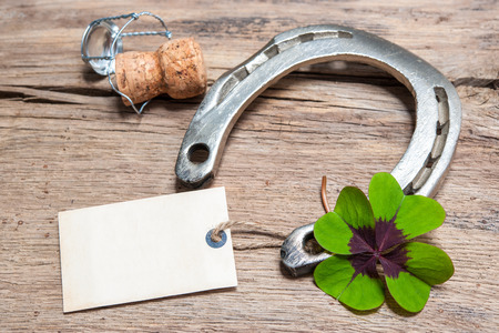 fourleaved: Horseshoe, shamrock and champagne cork with empty tag on old wooden