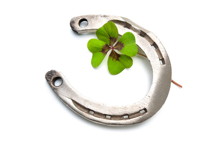 Horseshoes and clover with four leaf on white background photo
