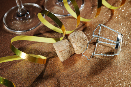 good fortune: Cork from champagne bottle and two glasses on golden background Stock Photo