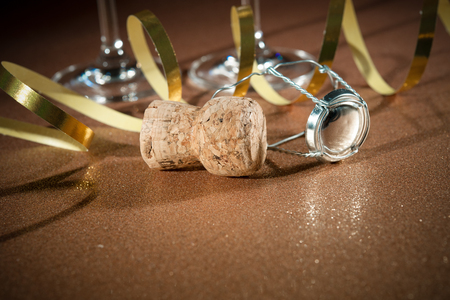 Cork from champagne bottle and two glasses on golden background photo