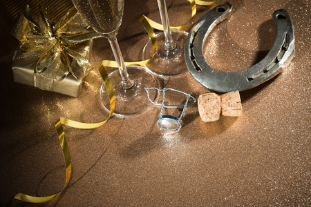 charms: Cork from champagne bottle with a horseshoe in front of two glasses and streamers