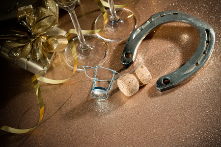 mojo: Cork from champagne bottle with a horseshoe in front of two glasses and streamers
