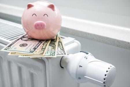 thermostat de chauffage avec tirelire et argent, chauffage coûte cher notion Banque d'images