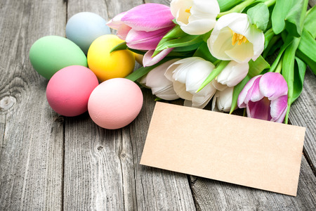 Easter eggs and tulips with a tag on wooden background photo