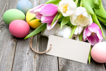 huevos de pascua: Huevos de Pascua y tulipanes con una etiqueta sobre fondo de madera