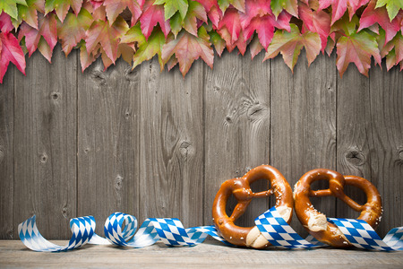 Bavarian pretzels with ribbon on wooden board. Background for Oktoberfest photo