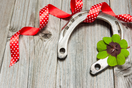 Holidays background with horseshoe, shamrock and red ribbon on old wooden photo