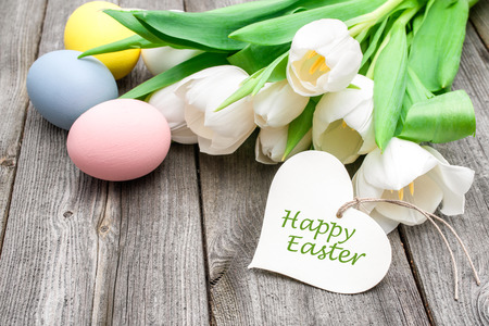 Easter eggs and tulips with a tag on wooden background Stock Photo - 32541655