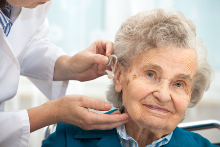 Doctor inserting hearing aid in seniors ear photo