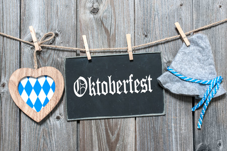 Message, bavarian hat and heart hanging on the clothesline against wooden board. Background for Oktoberfest photo