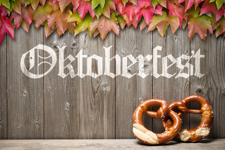 Bavarian pretzels with ribbon on wooden board. Background for Oktoberfest