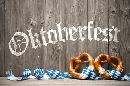 Bavarian pretzels with ribbon on wooden board. Background for Oktoberfest